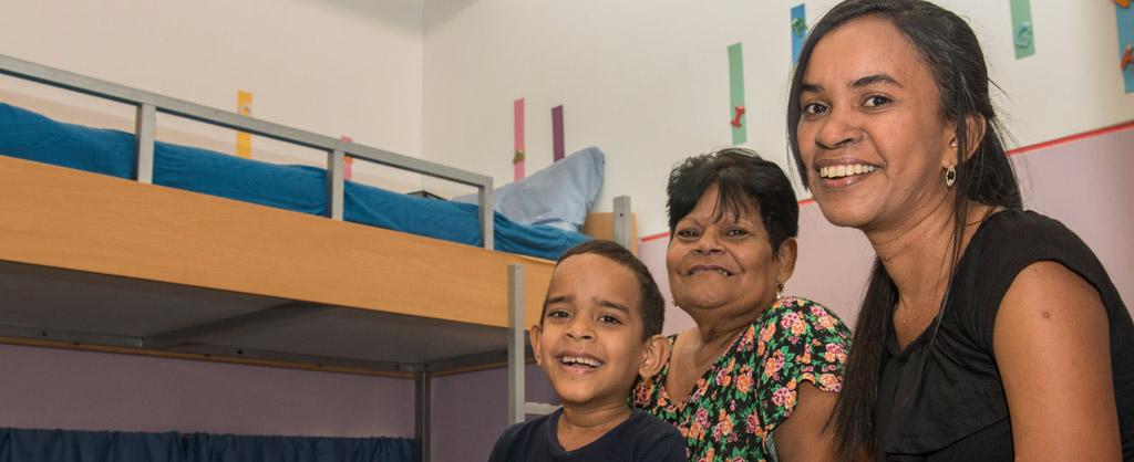 Un niño, su madre y abuela sonrientes.