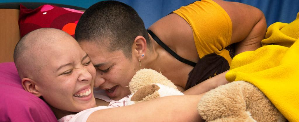 Niña con su madre riendo a carcajadas mientras la madre le hace cosquillas a la niña.