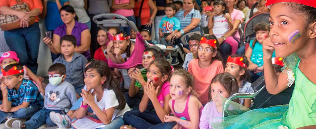 Muchos niños aparecen mirando algo que esta sucediendo frente a ellos. Tienen las caras pintadas y se ven felices y entretenidos.