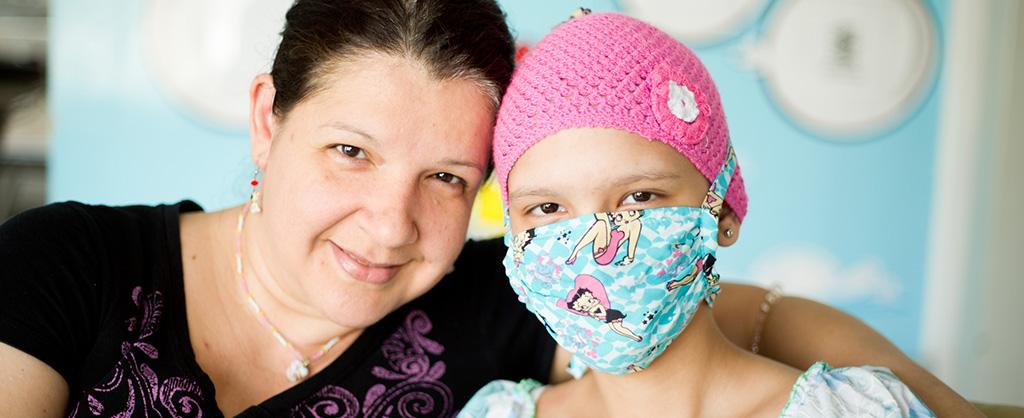Una niña con gorrito rosado tiene su carita tapada con un tapabocas. Esta al lado de su madre quien la abraza.
