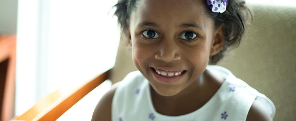 Una niña de nombre Luz Mary sonríe mientras mira a la cámara.