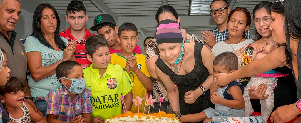 Un grupo de niños y adultos celebran el cumpleaños número 16 de una jovencita. Ella se alista para soplar las velas en el pastel.