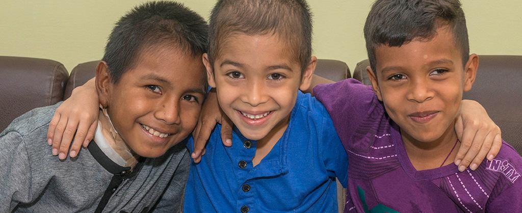 Tres niños muy sonrientes se abrazan mientras posan para la cámara.