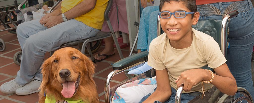 Un joven llamado Nixon aparece junto a un perro labrador, una de las mascotas de la Universidad Canina.