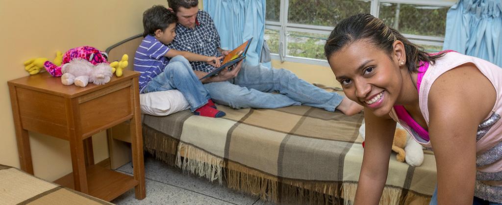En una habitación aparecen un padre y su hijo recostados leyendo un libro mientras su madre organiza algunas cosas y sonríe a la cámara.