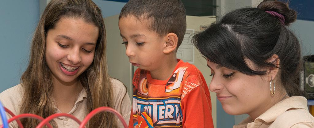 Dos jovencitas aparecen junto a un pequeño que parece estar recibiendo tratamiento médico.