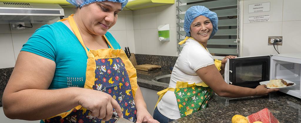 Dos señoras sonríen, mientras preparan una comida en la cocina.