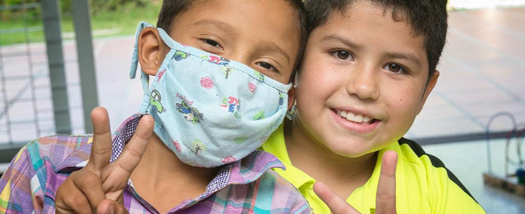 Dos niños hacen el símbolo de la paz con sus manos; uno de ellos usa un tapabocas.