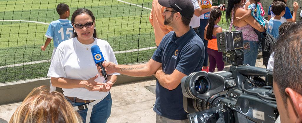 Mientras un juego de futbol se lleva a cabo, aparece detrás de la portería una mujer que está siendo entrevistada por un reportero que sostiene un micrófono. Se ve la cámara a mano derecha de la fotografía.