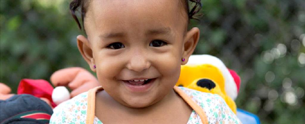 Una pequeña niña de vestido de flores sonríe. Detrás de ella se ven unos muñecos de peluches.