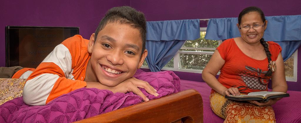 En una habitación se encuentra un nono encima de la cama mientras su madre sostiene un libro abierto. Ambos sonríen.